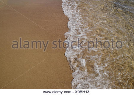 Waves lapping on the sandy shore - Stock Photo