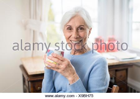 Portrait of smiling senior woman at home holding cup - Stock Photo