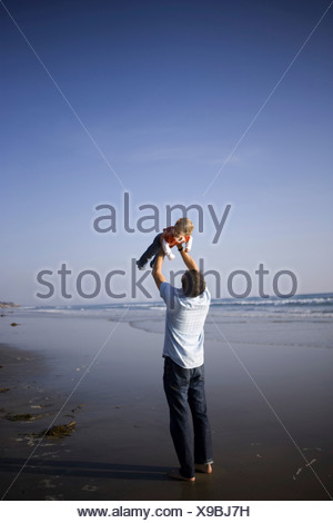 Father lifting baby daughter on beach - Stock Photo