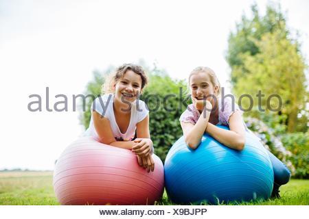 Portrait of two tween girls on exercise balls in garden - Stock Photo