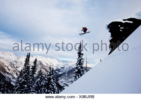 A athletic skier jumping off a cliff in the backcountry in Colorado. - Stock Photo