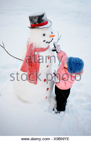 Young girl decorates a snowman with red scarf and black top hat, Alaska - Stock Photo