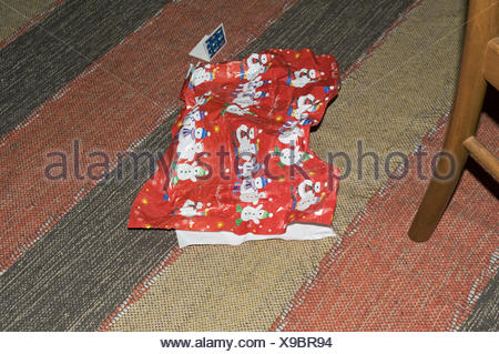 Present paper laying on carpet floor - Stock Photo