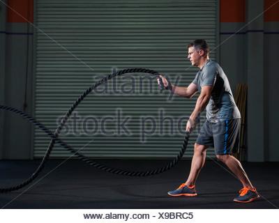 USA, California, Laguna Niguel, mature man exercising with rope - Stock Photo