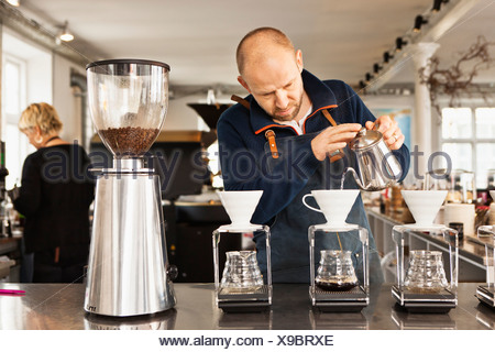 Barista pouring boiling water into coffee filters - Stock Photo
