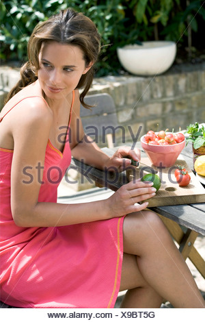 A DayYourself: Female brunette hair tied back loosely wearing short pink sundress orange detail, sitting at wooden table - Stock Photo