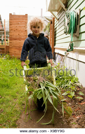 Young boy pushing wheelbarrow full of vegetables - Stock Photo