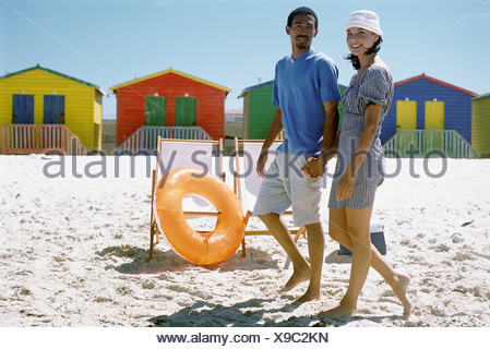 Couple walking hand in hand at the beach, smiling at camera, colorful beach huts in background - Stock Photo
