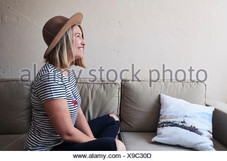 Woman sitting on sofa, smiling, side view - Stock Photo