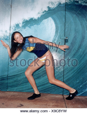 Female long wet brunette hair wearing black surfers shoes white and yellow bikini bottoms and blue and yellow vest top standing - Stock Photo