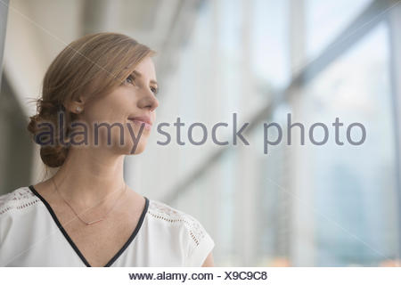 Portrait pensive businesswoman looking out window - Stock Photo