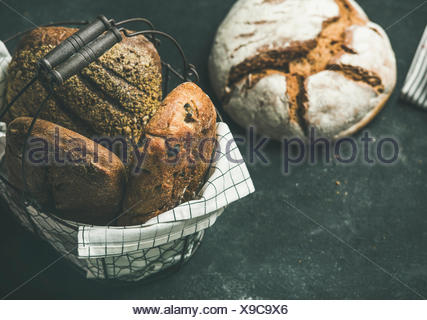 Various bread selection. Rye, wheat and multigrain rustic bread loaves on kitchen towels over black background, copy space - Stock Photo