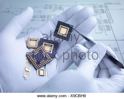 Electronic components held in hand in laboratory, close up - Stock Photo
