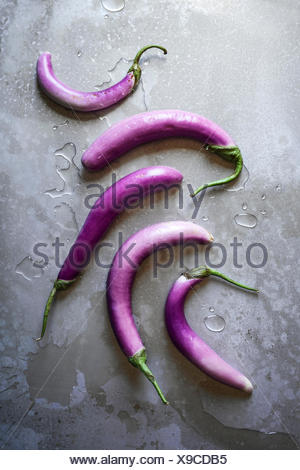 A layout of rich, purple, Asian eggplants with water on a textured wooden surface - Stock Photo
