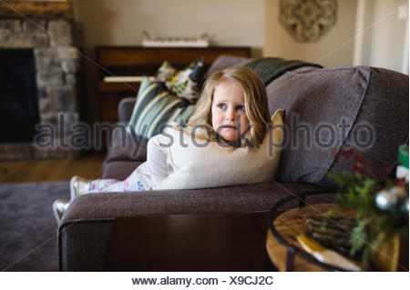 Fearful girl looking sideways from sofa - Stock Photo