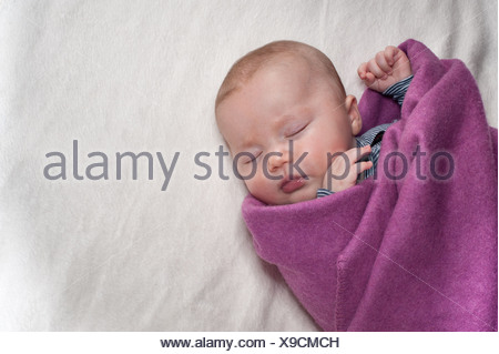 Newborn sleeping on lilac blanket - Stock Photo