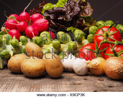 Fresh vegetables on a rustic wooden table, healthy eating concept - Stock Photo