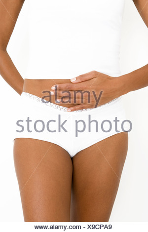 A woman with her hand resting on her stomach - Stock Photo