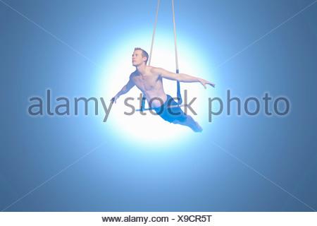 Man balancing on trapeze - Stock Photo