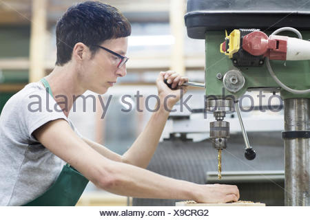 Woman in workshop using drilling machinery - Stock Photo