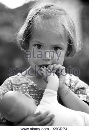 Little girl holding baby doll, portrait, b&w - Stock Photo