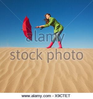 Woman holding red umbrella in the desert - Stock Photo