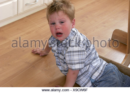 Little boy throwing a tantrum. The toddler child is weaning, whining and sobbing on the floor. - Stock Photo