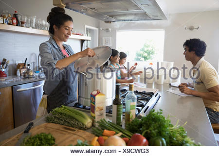 Family preparing vegetable stock in kitchen - Stock Photo
