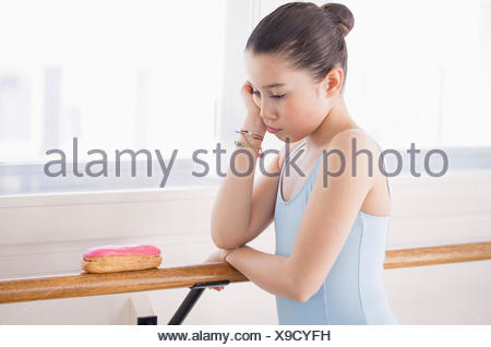 Girl looking displeased with eclair - Stock Photo