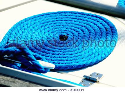 Close-Up Of Coiled Rope Tied Up With Mooring Cleat - Stock Photo