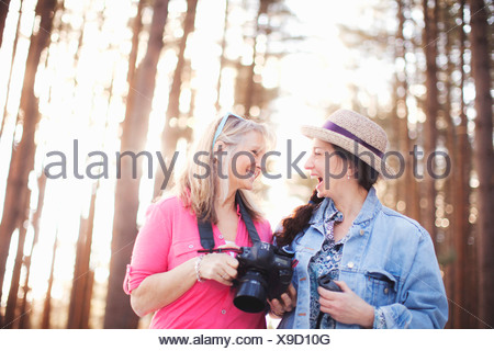 Two mature female bird watchers in forest - Stock Photo