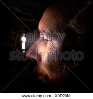 Man looking through a keyhole in a door - Stock Photo