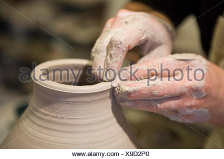 Close up of male potter's hands shaping clay pot on pottery wheel in workshop - Stock Photo