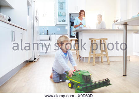 Women cooking in kitchen while boy plays with toy tractor on floor - Stock Photo