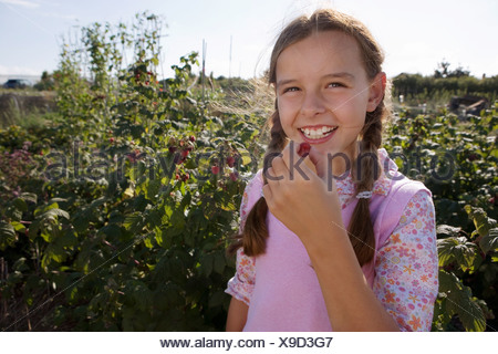 Girl 9 11 eating fresh fruit from garden smiling portrait - Stock Photo