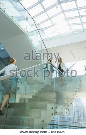 Businesswomen walking on steps in office - Stock Photo