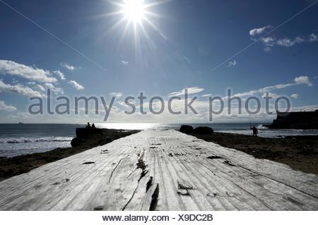 Boardwalk Leading Towards Lake Against Sky On Sunny Day - Stock Photo