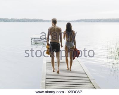 Rear view of couple wearing swimsuits, walking down pier carrying towels, Copenhagen, Denmark - Stock Photo