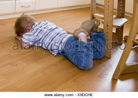 Little child throwing a temper tantrum at home. The toddler is down on the floor, hiding his face, out of control and misbehaving. - Stock Photo