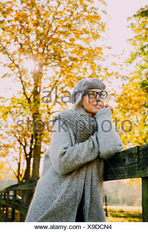 Portrait of woman wearing grey knitwear in an autumnal park - Stock Photo