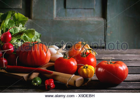 Heap of fresh ripe colorful vegetables tomatoes, chili peppers, green onion and bunch of radish on wooden chopping board over ol - Stock Photo