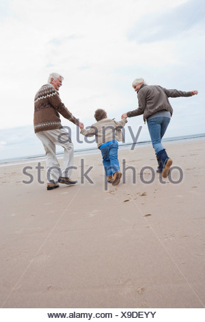 Grandparents And Grandson Running Along Winter Beach - Stock Photo