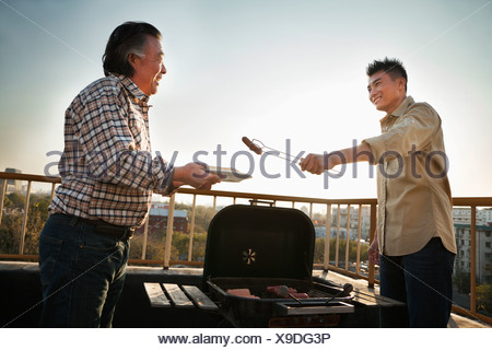 Son giving sausage to his father over the barbeque - Stock Photo