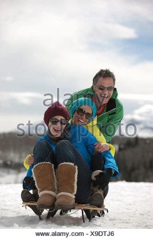 Three friends sitting on sledge in snow - Stock Photo