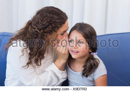 Mother and daughter whispering - Stock Photo