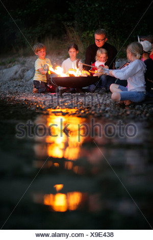 Children and man grilling at Lake Starnberg, Bavaria, Germany - Stock Photo