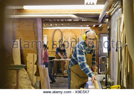 Senior carpenter using equipment in workshop - Stock Photo