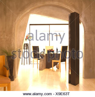 Concrete walls and polished floor in dining area with arched doorway and tall speaker in late eighties Californian house - Stock Photo