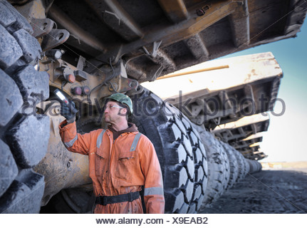 Coal miner inspects dumper truck tyre tread in surface coal mine - Stock Photo