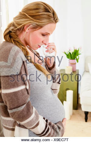 Tearful pregnant woman touching stomach in living room - Stock Photo